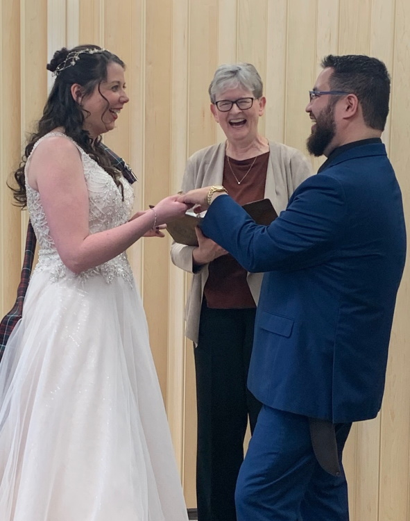 Wedding couple with female reverend in the middle